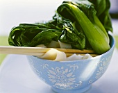 Pak choi with rice noodles in small bowl