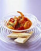 Shrimps in tomato sauce in a glass bowl with pita bread