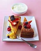Two pieces of polenta cake with berries and whipped cream