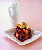 Ein Stück saftiger Beerenkuchen auf einem quadratischen Teller