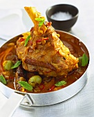 Braised lamb shank with mint in a frying pan (India)