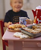 Small boy at table with cakes, pastries and cup