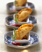 Three deep-fried won tons with potato filling in chili dip