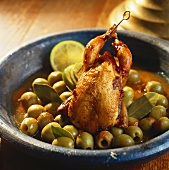 A quail with green olives in tomato sauce
