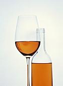 Ein Glas Rosé mit einer Roséflasche