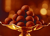 A pyramid of chocolate truffles in a golden bowl