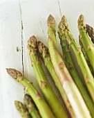Green asparagus on white painted wooden background