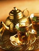 Peppermint tea in glasses and pot on gold tray