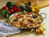 Paella with king prawns in pan, surrounded by ingredients
