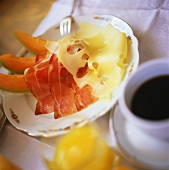 Breakfast of melon, bacon, cheese, coffee and orange juice