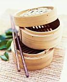 Two steaming baskets and chopsticks on bamboo mat