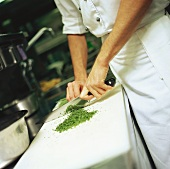 Chef chopping herbs in a kitchen