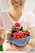 Woman holding bowl of sugared fresh berries
