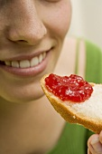 Woman eating a slice of white bread with strawberry jam