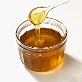 Honey running from spoon into jar
