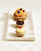 Three muffins with different creams and chocolate beans
