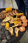 Chicken pieces, corncobs, tomatoes & sausages on a barbecue