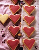 Heart-shaped biscuits with mango jam and glacé icing
