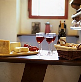 Cheese board with bread basket and red wine