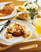 Breakfast tray with scrambled egg, juice, croissant and jam