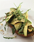 Slice of bread topped with avocado and rocket