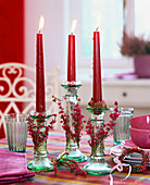 Glass candlestick with red candles, coffee things behind