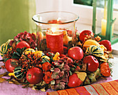 Autumn wreath around glass with red candle