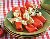 Red napkins with checked bows on green plates