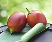 Two tamarillos on banana leaf