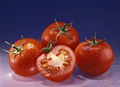 Three whole tomatoes and half of a tomato