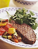 Grilled peppered steak with watercress and vegetables