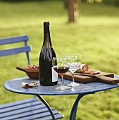 Blue table with red wine & hard cured sausage in open air