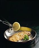 Wiener Schnitzel in a frying pan