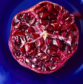 Half a pomegranate against blue background