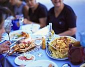Menschen am Tisch mit Meeresfrüchte- & Fischgerichten