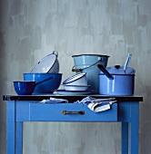 Blauer Küchentisch mit verschiedenen emaillierten Töpfen
