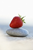 A strawberry on a stone