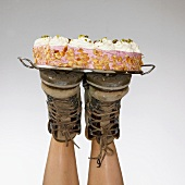 Two feet balancing a cream cake on a tray