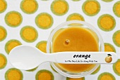 Orange dessert in small bowl with spoon