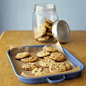 Chocolate chip cookies on baking tray and in jar