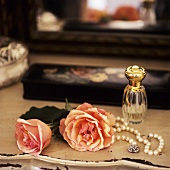 Roses, string of beads and perfume
