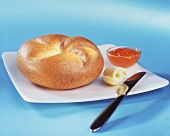 Bread roll with butter curl and jam
