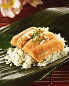 Salmon with lime and rice on banana leaf