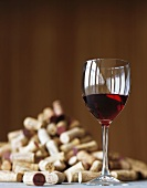 A glass of red wine and lots of corks