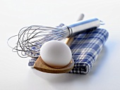 A white egg on a wooden spoon and an egg whisk