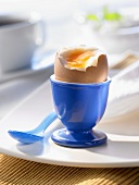 Soft-boiled breakfast egg in a blue eggcup