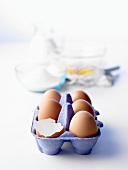 Egg box with brown eggs, baking ingredients behind