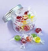 Verschiedene Bonbons in einem Schraubglas und davor