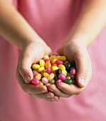 Assorted jelly beans, in a child's hands