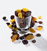 Raisins and sultanas in and beside a small glass